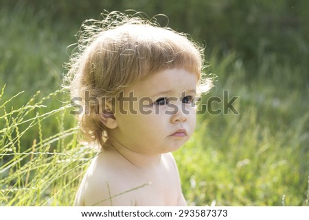 Portrait of small pretty happy child boy with blonde curly hair looking away and sitting on fresh green grass outdoor on natural background, horizontal picture - stock photo