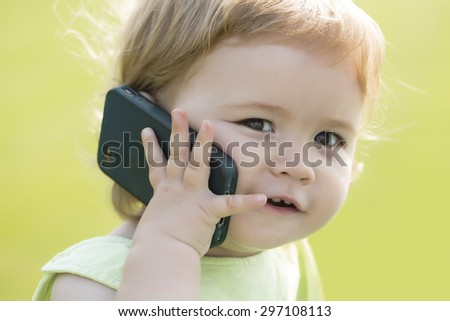Portrait of small pretty smiling baby boy with blonde curly hair and cute face holding and speaking on black mobile phone sunny day outdoor on green grass background, horizontal picture - stock photo