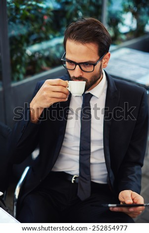 Portrait of smart attractive businessman in glasses drink coffee during his outdoors breakfast, handsome executive holding tablet pc having a coffee - stock photo