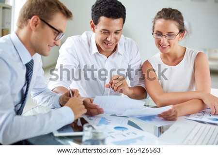 Portrait of smart business partners discussing papers at meeting - stock photo
