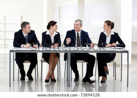 Portrait of smart business people sitting at table and interacting - stock photo