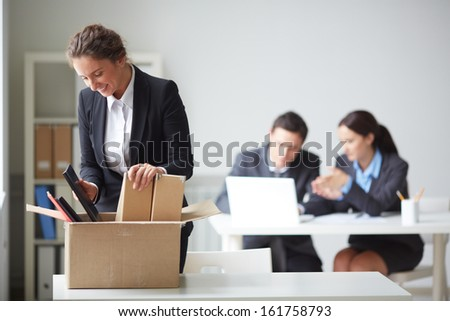 Portrait of smart businesswoman packing her things on background of working colleagues - stock photo