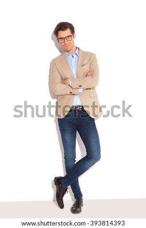 portrait of smart casual man wearing glasses, posing in white studio background with hands and legs crossed - stock photo