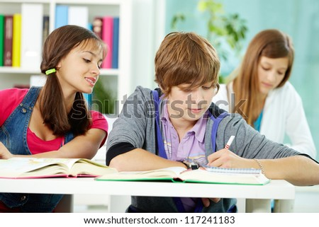 Portrait of smart classmates writing test during lesson - stock photo