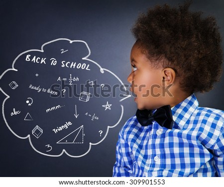 Portrait of smart curly African American schoolboy in the school on math lesson, solving task near chalkboard - stock photo