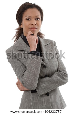 Portrait of smart ethnic businesswoman standing with hand on chin. - stock photo