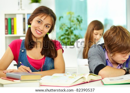 Portrait of smart girl looking at camera during lesson with classmates near by - stock photo