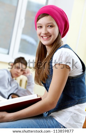 Portrait of smart girl looking at camera with her classmate on background - stock photo
