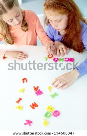 Portrait of smart girls making word �¢??school�¢?? - stock photo