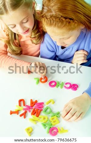Portrait of smart girls making word ?school? - stock photo