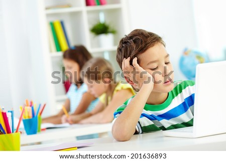 Portrait of smart lad at workplace networking with two classmates drawing on background - stock photo