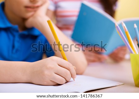 Portrait of smart lad drawing with pencils at lesson - stock photo