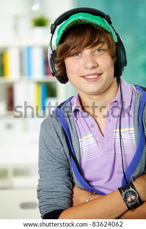 Portrait of smart lad in headphones looking at camera - stock photo