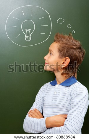 Portrait of smart lad looking at blackboard with drawn lamp on it - stock photo