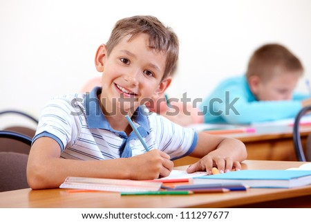 Portrait of smart lad looking at camera with classmates on background - stock photo