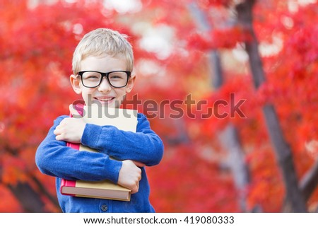 portrait of smart little boy in glasses holding book ready for school in beautiful autumn park - stock photo