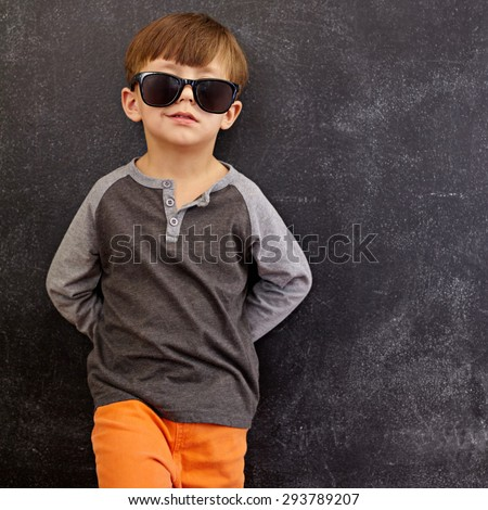 Portrait of smart little boy wearing sunglasses smirking. Cool kid in shades leaning on a blackboard looking at camera smiling with copy space. - stock photo