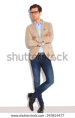 portrait of smart man wearing glasses posing in white studio background with hands and legs crossed, while looking away from the camera - stock photo