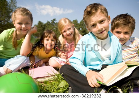Portrait of smart preschooler holding book with his friends on background in natural environment - stock photo