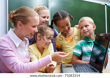 Portrait of smart pupils sitting in the classroom and looking at camera - stock photo
