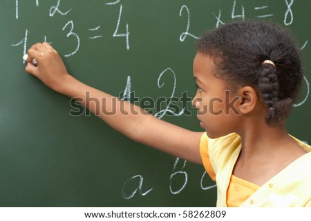 Portrait of smart schoolchild standing at blackboard and doing sums - stock photo