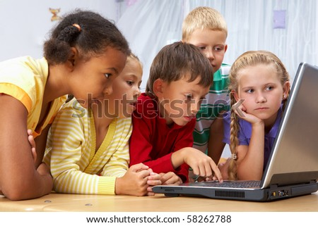Portrait of smart schoolgirls and schoolboys looking at the laptop - stock photo