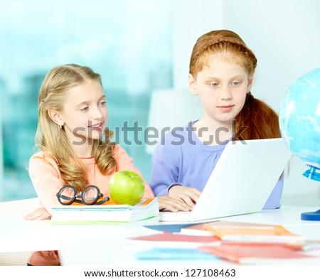 Portrait of smart schoolgirls sitting in classroom in front of laptop - stock photo