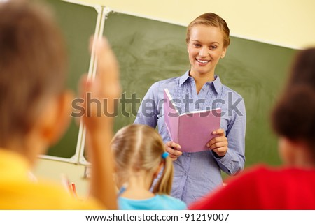Portrait of smart teacher with exercise book looking at schoolkids in classroom - stock photo