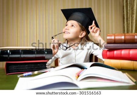 Portrait of smart thoughtful girl posing at desk in graduation cap - stock photo