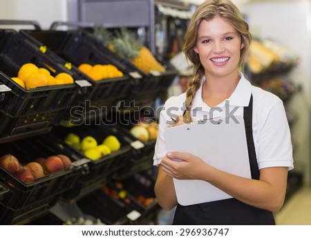 Portrait of smiling a staff man writing on notepd at supermarket - stock photo