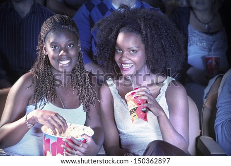 Portrait of smiling African American female friends with drink and popcorn watching movie in theater - stock photo