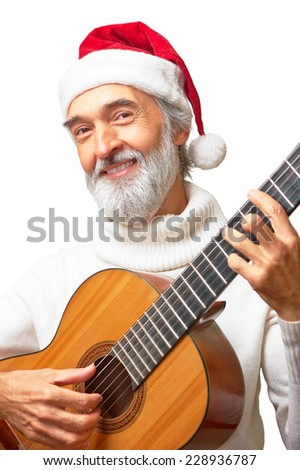 portrait of smiling Aged bearded man in santa's red hat playing the acoustic guitar isolated on white background  - stock photo