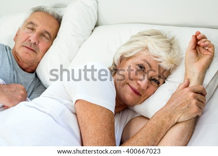 Portrait of smiling aged woman with man relaxing on bed at home - stock photo