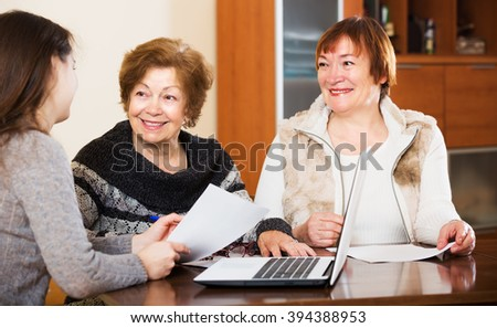 Portrait of smiling aged women with papers and agency employee - stock photo