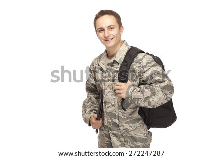 Portrait of smiling air force airman college student with shoulder bag and digital tablet against white background - stock photo
