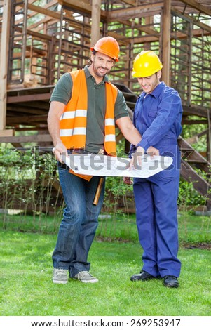 Portrait of smiling architect with colleague explaining blueprint outside incomplete wooden cabin at construction site - stock photo