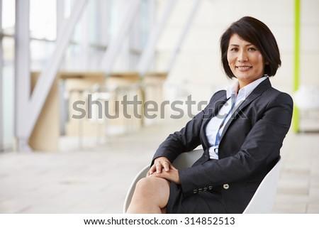 Portrait of smiling Asian businesswoman, sitting - stock photo