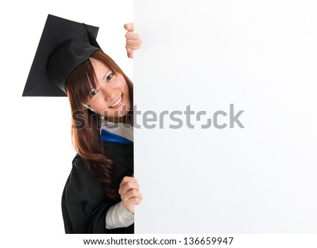 Portrait of smiling Asian female student in graduate gown peeking, hiding behind a white card, isolated on white background - stock photo