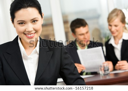 Portrait of smiling Asian woman on the background of working business team - stock photo