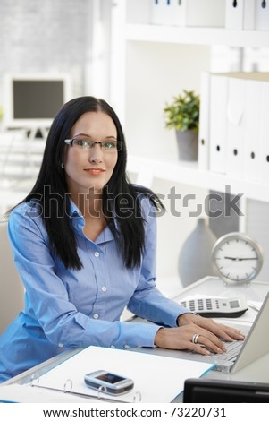 Portrait of smiling assistant girl wearing glasses, sitting at office desk with laptop computer, looking at camera.? - stock photo