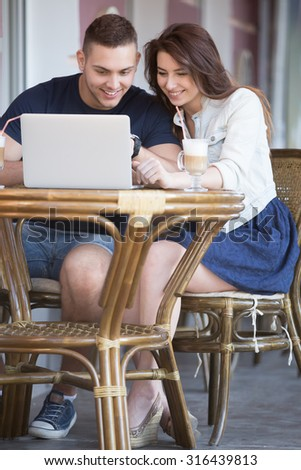 Portrait of smiling attractive young man and beautiful woman in casual clothes sitting in street cafe with rattan furniture drinking coffee, using laptop, looking at screen with happy expression - stock photo