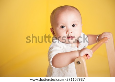 portrait of smiling baby boy isolated on yellow background - stock photo
