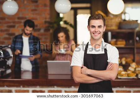 Portrait of smiling barista with arms crossed in front of customers at coffee shop - stock photo