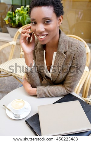Portrait of smiling beautiful african american business woman in phone call conversation, in city coffee shop using a smart phone, exterior. Professional black woman, technology lifestyle outdoors. - stock photo