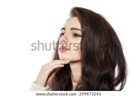 Portrait of smiling beautiful brunette model with freckles and long hair in yellow sweater. With hand on her chin. Isolated on a white background. - stock photo
