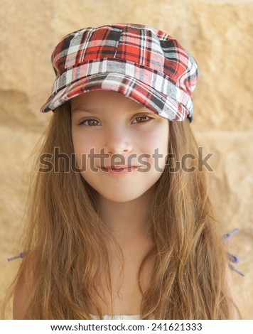 Portrait of smiling beautiful little girl in hat on background of wall. - stock photo