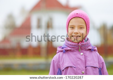 Portrait of smiling beautiful little girl in pink hat and jacket on red background of house. - stock photo