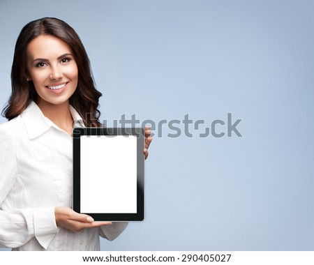 Portrait of smiling beautiful young brunette businesswoman showing blank no-name tablet pc monitor, over grey background, with copyspace area for slogan or text message - stock photo