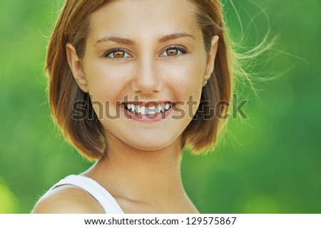 Portrait of smiling beautiful young woman, against background of summer green park. - stock photo