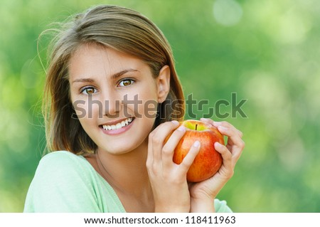 Portrait of smiling beautiful young woman close up with apple, against background of summer green park. - stock photo